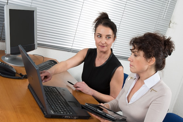 Two women chat to each other in the office with one woman having her laptop