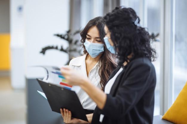 차트를 확인하고 사무실에서 비즈니스 동향을 논의하는 두 명의 여성.