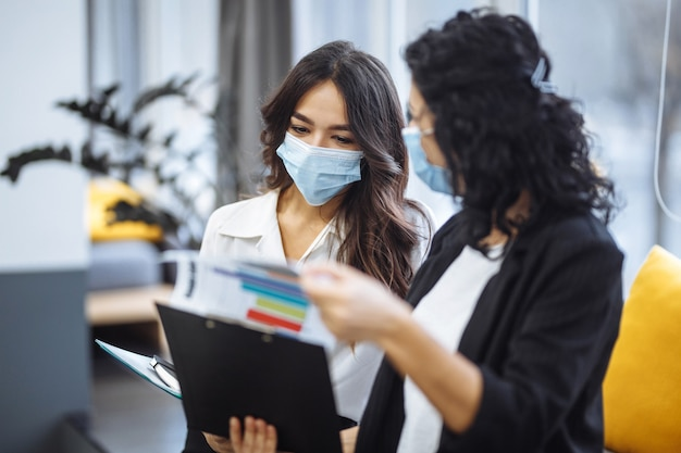 Two women checking charts and discussing business trends in the office. females colleagues wearing medical masks sit on the couch at a working place