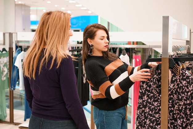 Two women choose clothes in a store