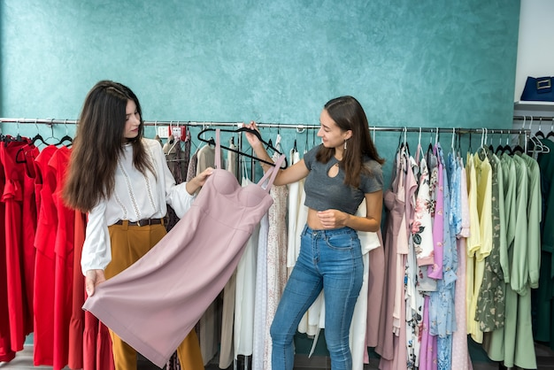 Two women choose modern dress in a store. black friday shopping concept