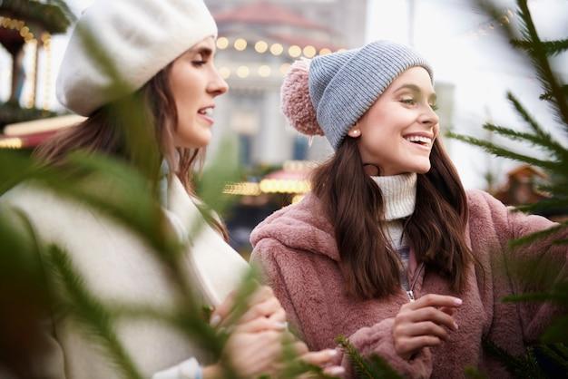 크리스마스 시장에서 크리스마스 트리를 선택하는 두 여자