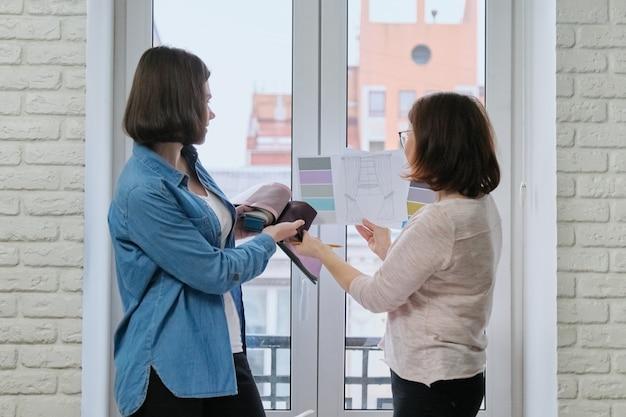 커튼을 위해 직물을 선택하는 두 여자. 여성 섬유 디자이너, 장식가 및 직물이있는 고객 시계 팔레트, 모델 및 직물 선택
