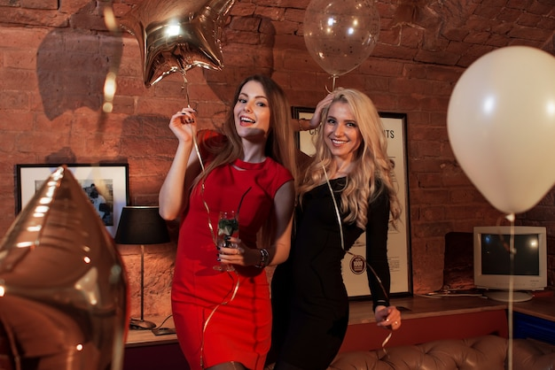 Two women in cocktail dresses posing with balloons at birthday party in stylish cafe.