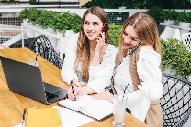 2人の女性の同僚がコンピューターで一緒に作業し、そのうちの1人がノートにメモを書きます