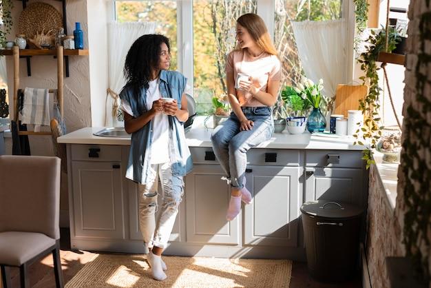 キッチンでコーヒーを飲みながら会話する2人の女性