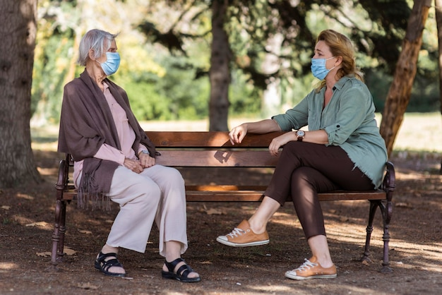 Two women conversing with medical masks outdoors at nursing home