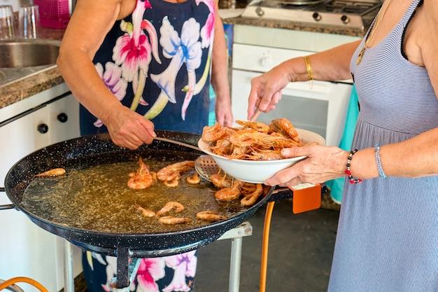 スペインのパエリアを準備するためにエビを調理する2人の女性、顔は表示されていません