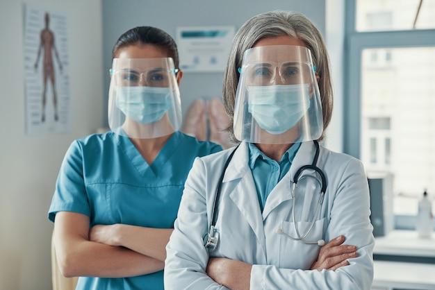 Две женщины-коллеги в медицинской форме и защитной спецодежде, скрестив руки, смотрят в камеру во время работы в больнице
