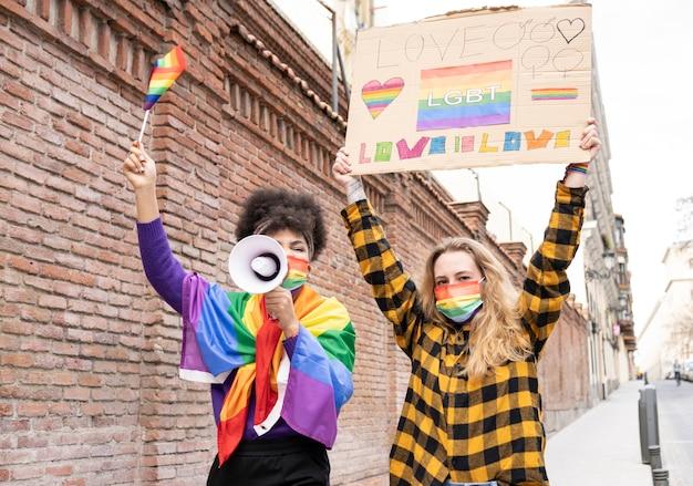 ゲイプライドの旗を掲げて、ゲイプライドの日にデモンストレーションを行う2人の女性