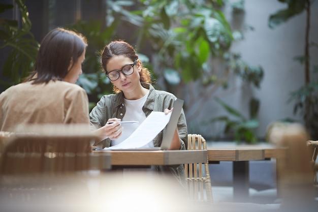 Две женщины обсуждают бизнес-проект в кафе