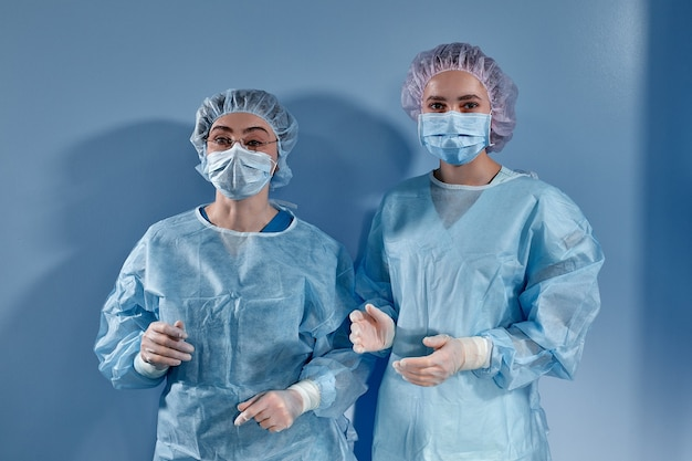 Two women doctors surgeons standing before surgery and looking at the camera on blue surface