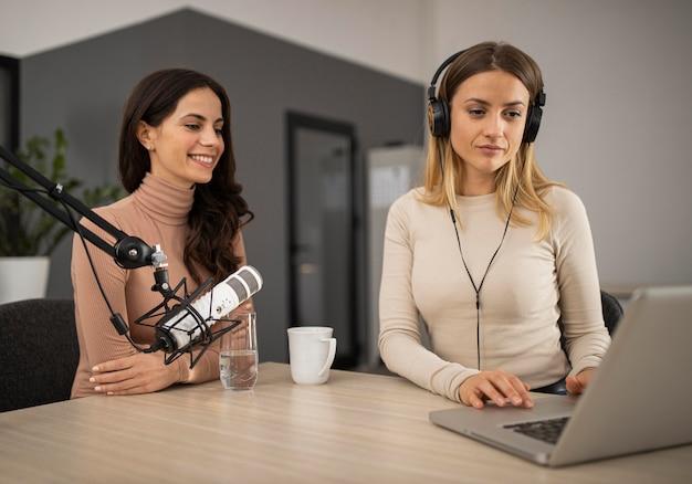 Две женщины делают радио-шоу вместе с микрофоном и ноутбуком