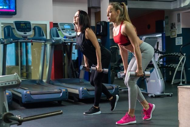Two women doing fitness training together in gym