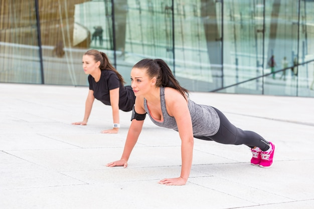 Two women doing push-ups exercises