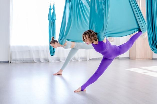 フィットネストレーニング健康フライヨガの概念でフライヨガを使用してストレッチ運動をしている2人の女性