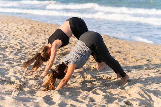 Two women doing yoga poses on the beach