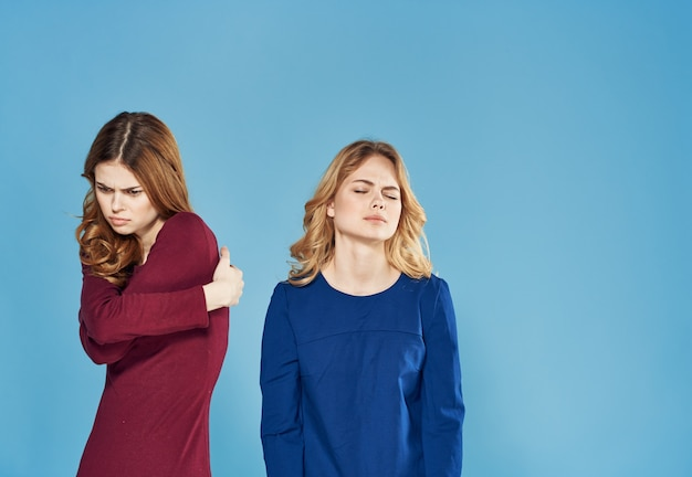 Two women in dress conflicts quarrel emotions blue background
