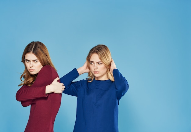 Two women in dress conflicts quarrel emotions blue