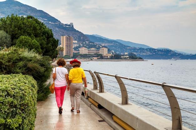 Две красочно одетые женщины гуляют по набережной в монако в ясный летний день