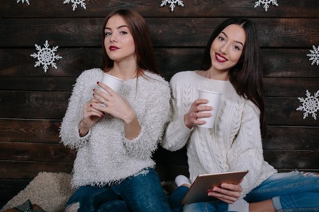 2人の女性が温かい飲み物を飲み、タブレットで何かを見ている