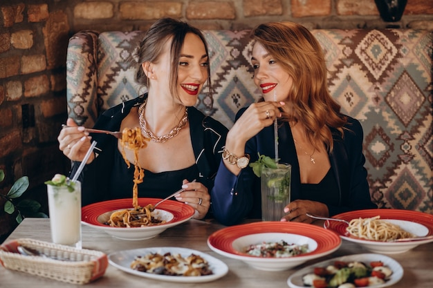 Две женщины едят пасту в итальянском ресторане