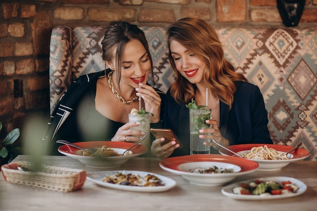 Two women eating pasta in an italian restaurant