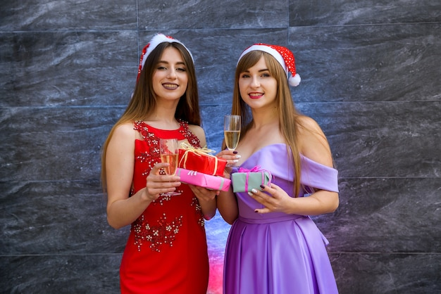 Two women in elegant evening dresses looking in gift bag. new year party celebration