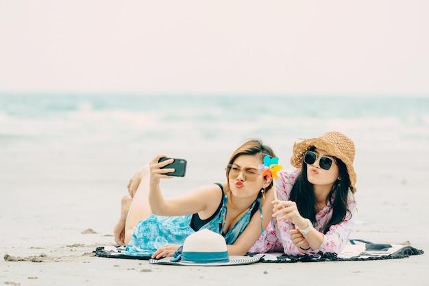 Two women enjoying beach relaxing joyful in summer by tropical blue water.model on travel wearing beach hat.