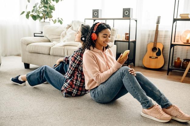2 人の女性が床に背中合わせに座って音楽を楽しんでいます。イヤホンをしたかわいいガールフレンドが部屋でくつろぎ、音の愛好家がソファで休んで、女性の友達が一緒にレジャーをする