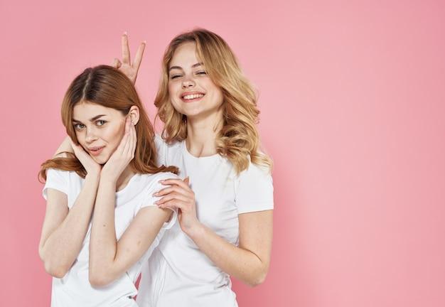 Две женщины модной одежды весело обнимаются за заботливую розовую стену.