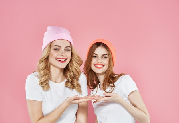 Two women in fashionable clothes pink hats studio cropped view.