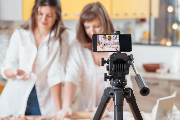 스마트 폰에서 조리 과정을 촬영하는 두 여자