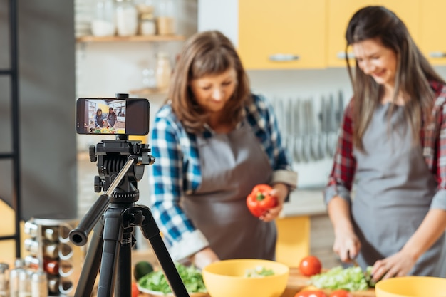 Two women filming cooking process on smartphone