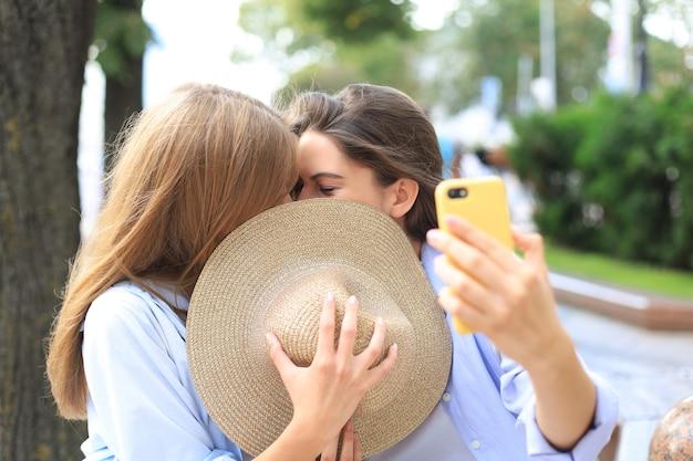두 여자 친구가 재미를 위해 서로 키스하고 있습니다.
