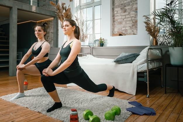 自宅で2人の女友達が笑顔でトレーニング