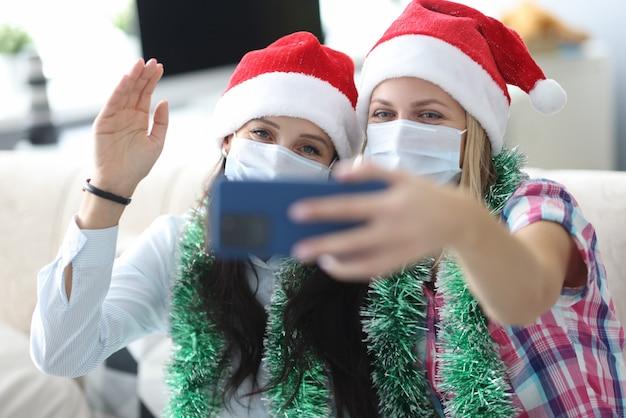 Две подруги в защитных масках и красных шляпах санта-клауса фотографируются на портрете по телефону