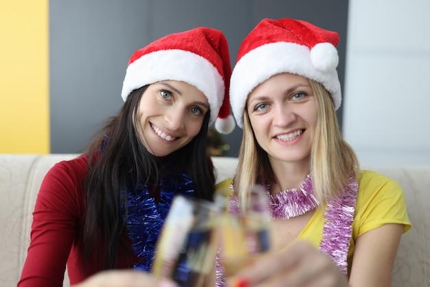 Две подруги в новогодних шапках сидят дома на диване и пьют шампанское
