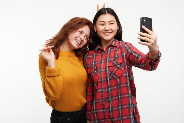 두 여자 친구. 스마트 폰에서 셀카 만들기. 소녀는 머리카락을 가지고 놀며 친구에게 뿔을 달았습니다. 노란색 스웨터와 체크 무늬 셔츠를 입고. 사람들이 개념. 흰 벽 위에 절연 스탠드