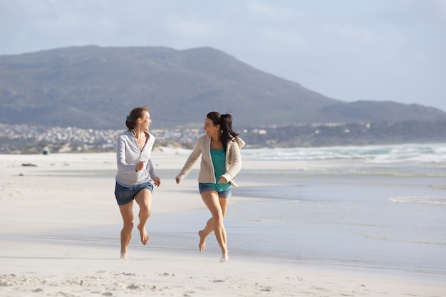 Two women friends running on the beach together