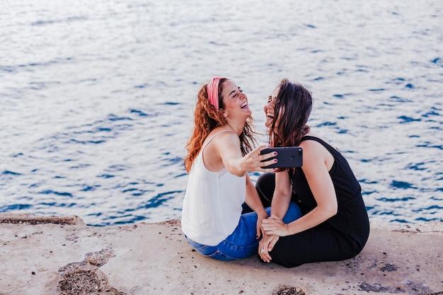 Две подруги сидят на пляже с помощью мобильного телефона
