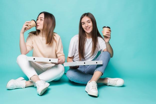 床に座っている2人の女性の友人は、ターコイズブルーの壁に隔離されたピザを食べに行くためにコーヒーを飲みます