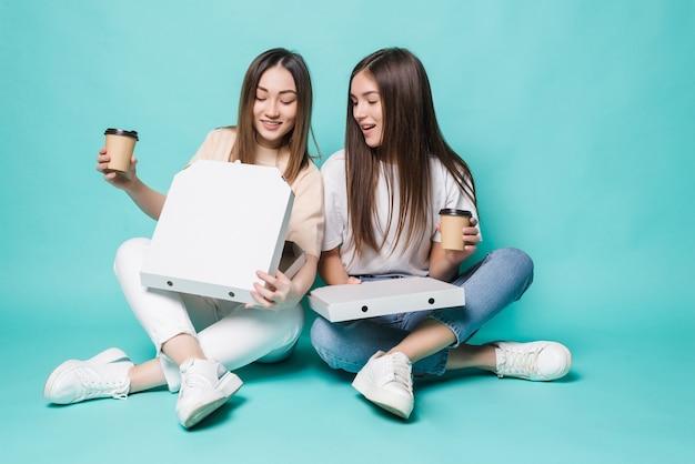 Две подруги сидят на полу, пьют кофе и едят пиццу, изолированные на бирюзовой стене