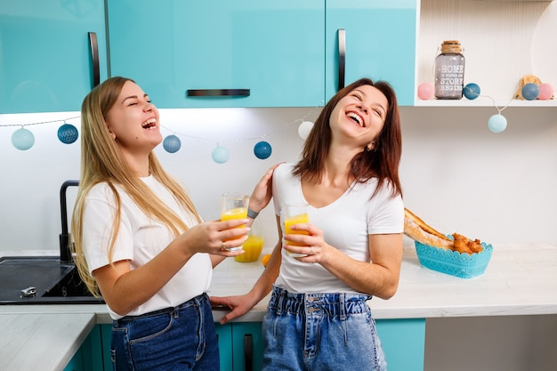台所に立ってオレンジジュースを飲んでいる2人の女性の友人。ガールフレンドは、キッチン、朝食でチャットし、秘密を共有します