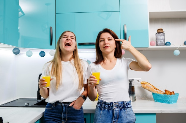Two women friends standing in the kitchen and drinking orange juice. girlfriends chat and share secrets in the kitchen, breakfast