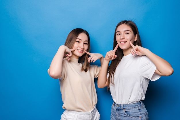 Two women girlfriends pointed in cheeks isolated on blue wall