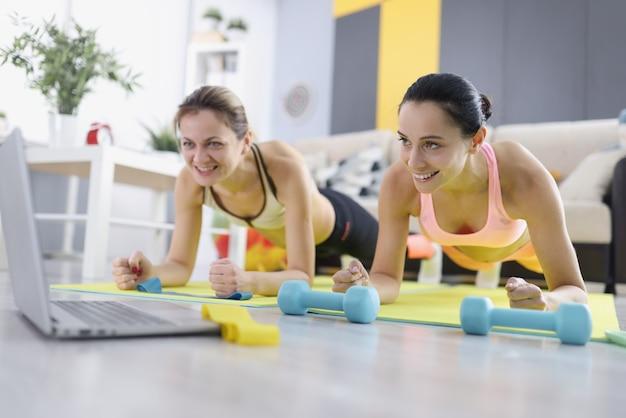 두 명의 여성이 집에서 운동을하고 판자 위에 서 있습니다. 검역 개념 중 온라인 스포츠