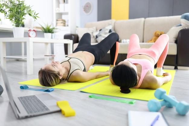 두 명의 여성이 집에서 운동을하고 엉덩이를 휘두 릅니다. 홈 개념에서 스포츠를 하