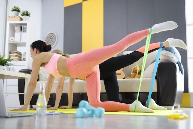 두 명의 여성이 집에서 운동을하고 신축성있는 밴드로 엉덩이를 휘두 릅니다. 피트니스