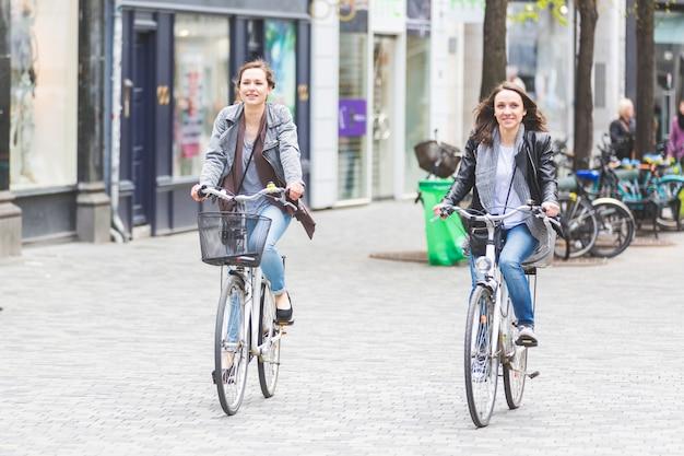 Two women going by bike in copenhagen.